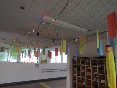 南棟玄関の七夕飾り 天井からたくさんの短冊や飾りが吊り下げられています 電飾を活用して天の川を表現しています