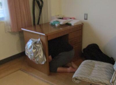 写真説明 地震発生時机の下に入って身を守る舎生