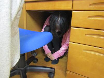 写真説明 机の下で地震から身を守る訓練中の舎生