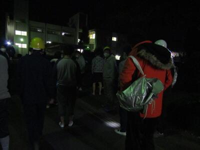 写真説明 建物の外へと避難する、訓練中の舎生・職員